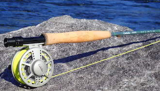 This best fly rod and reel combo photo shows the Cabela's Synch Fly Combo fly rod and reel on a rock near a river.
