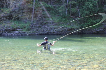This best wading boot photo shows a person wading in a river while wearing wading boots and waders while fly fishing.