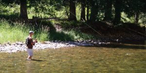 This best wading boots for the money fly fishing photo shows a fly fisherman wading in a river while wearing wading boots.