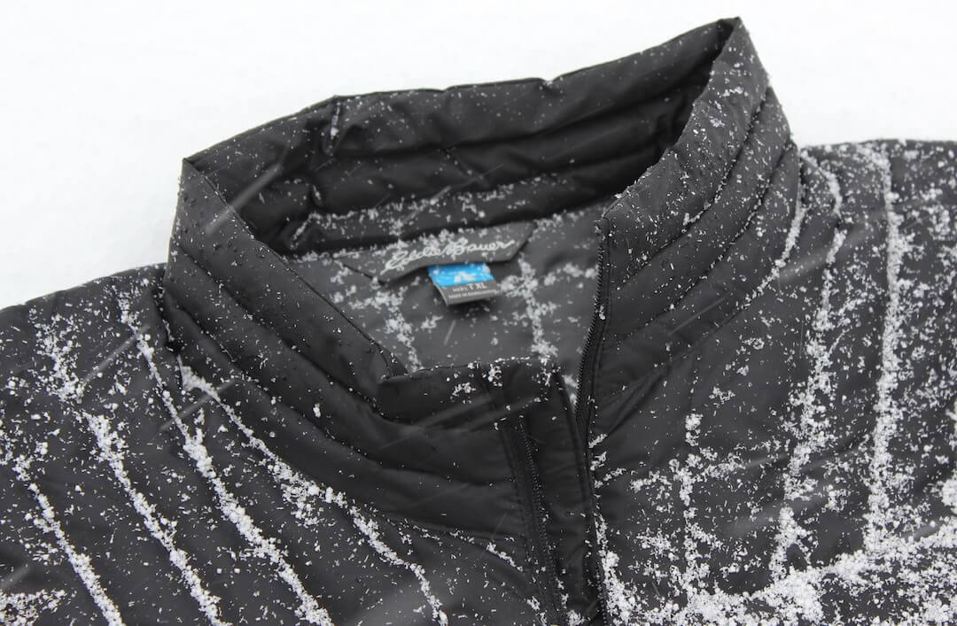 db36135bb54 this best down jacket image shows snow on the dwr waterproofing coating on  an Eddie Bauer