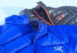 This down jacket product image shows a blue Arc'teryx Thorium AR men's down jacket next to a black Mountain Hardwear Ghost Whisperer men's down jacket.