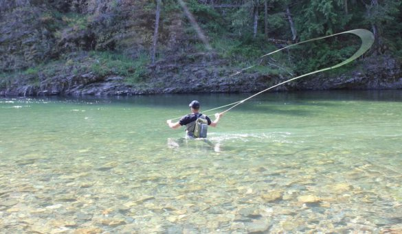 This image shows a fly fisherman wading deep in a river with a Simms Waypoint fly fishing sling pack.