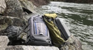This image shows fly fishing sling packs on the bank of a river.