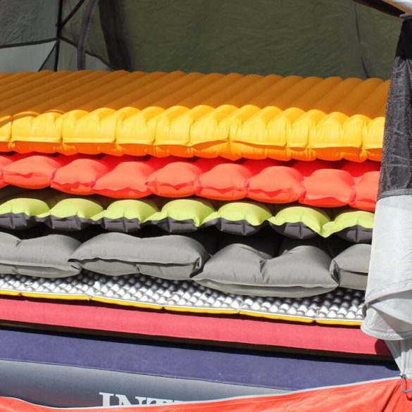 This best sleeping pad reviews photo shows several air mattresses and sleeping pads for camping and backpacking stacked up in a tent.