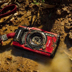 This image shows the Olympus Tough TG-5 waterproof camera on the ground in mud.