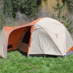 This image shows the Cabela's West Wind Dome Tent in the 6-person version outside at a camping site.