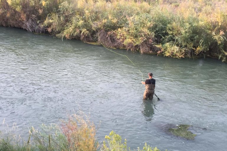 This image shows the Frogg Toggs Hellbenders fishing waders in action fly fishing on a river.