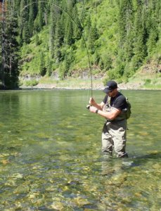 This image shows a man fishing in a river for trout while wearing the Orvis Silver Sonic Convertible-Top Waders.