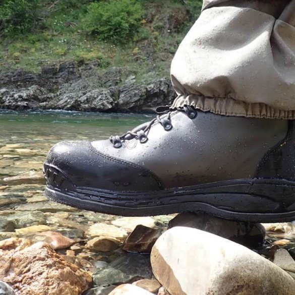 This image shows the Simms Freestone wading boot at the river's edge.