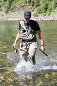 This image shows Chris Maxcer wading in a river wearing Simms Freestone Boots.
