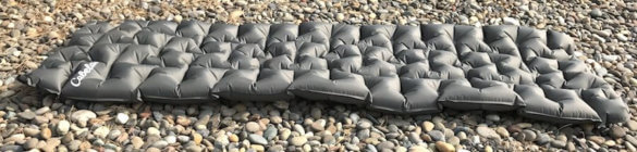 This image shows the Cabela's Ultralight Air Pad inflated on some rocks.