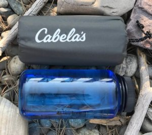This image shows the Cabela's Ultralight Air Pad packed up next to a water bottle.