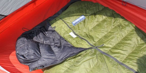 This review photo of the Feathered Friends Flicker quilt sleeping bag shows the Flicker 20 Nano in a tent partially unzipped.