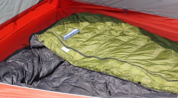 This image shows the Feathered Friends Flicker down quilt sleeping bag inside of a backpacking tent.