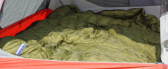 This photo shows the Feathered Friends Flicker 20 Nano Down Quilt Sleeping Bag unzipped on the floor of a backpacking tent.