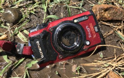 This image shows the Olympus Tough TG-5 waterproof camera in the mud on the ground.