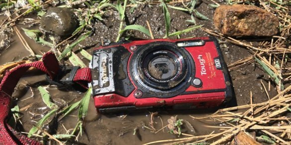 This image shows the Olympus Tough TG-5 camera in the mud.