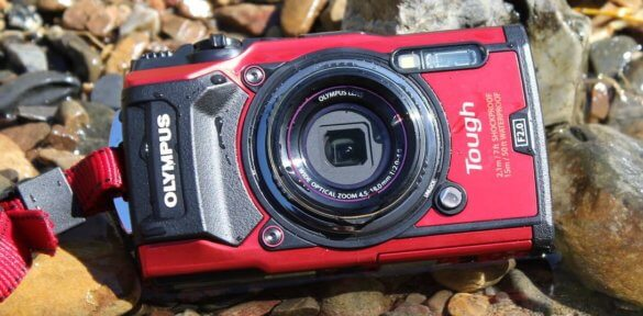 This image shows the Olympus Tough TG-5 waterproof camera on the bank of a river.
