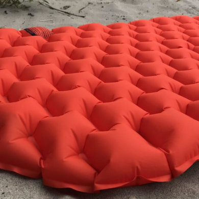 This image shows the REI Co-op Flash Insulated Air Sleeping Pad in a closeup on a beach.