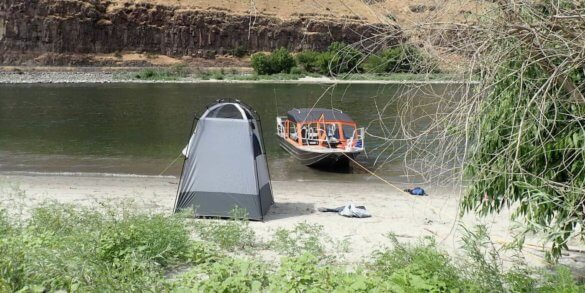 This photo shows the Cabela's Privy Shelter on the bank of a river next to a jet boat in the water.