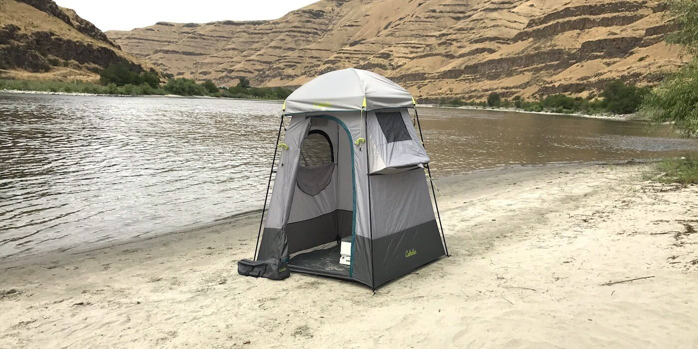 This image shows the Cabela's Privy Shelter on the bank of a river on a sandy beach.