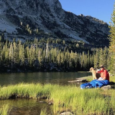 This photo shows a backpacker sitting by a mountain lake drinking coffee with the Sierra Designs Backcountry Quilt 700.