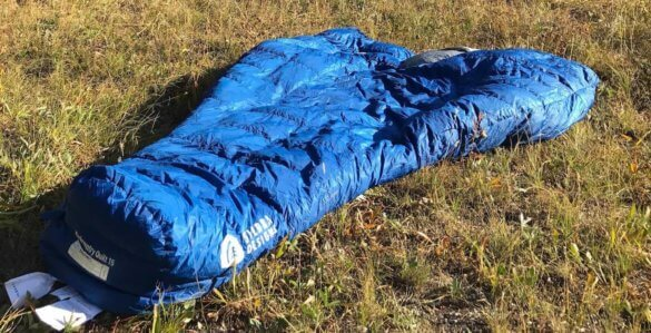 This image shows the Sierra Design Backcountry Quilt 700 on the ground in a high mountain meadow.
