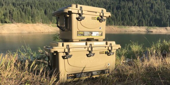 This image shows two Cabela's Polar Cap Equalizer Coolers on the bank of a river.
