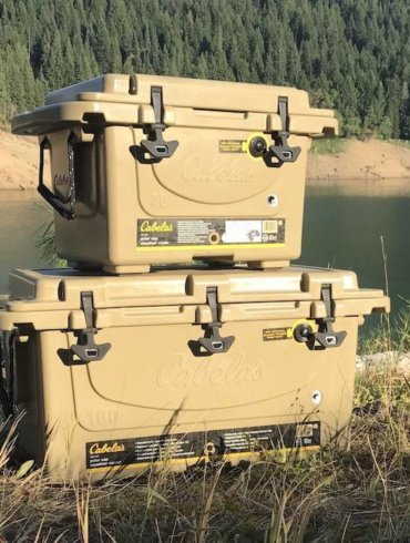 This image shows the Cabela's Polar Cap Equalizer Cooler on the bank of a lake.