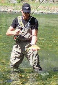 This image shows the Orvis Silver Sonic Convertible-Top Waders for fly fishing in use on a river.