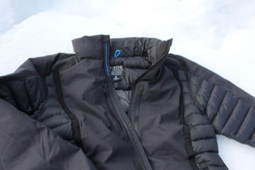 This image shows the KÜHL Firestorm Down Jacket on snow.