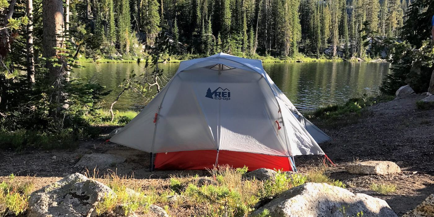 This photo shows the REI Co-op Quarter Dome 2 Tent near a mountain lake in a backpacking wilderness area.