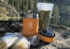 This backpacking gift idea shows the Hydro Flask Food Flask on a rock near a mountain lake.