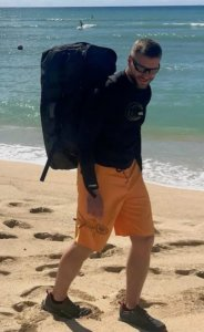 This photo shows the REI Big Haul Duffel bag being worn by the author while on a beach.