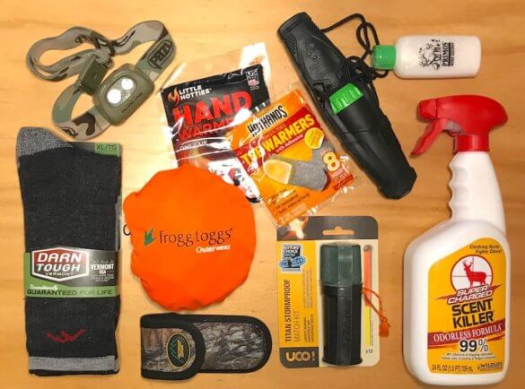 This photo shows stocking stuffers for hunters, including a deer call, wind checker, scent eliminator, wool socks, orange hunting vest, headlamp, and emergency matches.