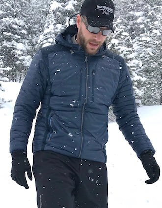 This photo shows a man wearing the men's KÜHL SPYFIRE HOODY down jacket outside in the snow.