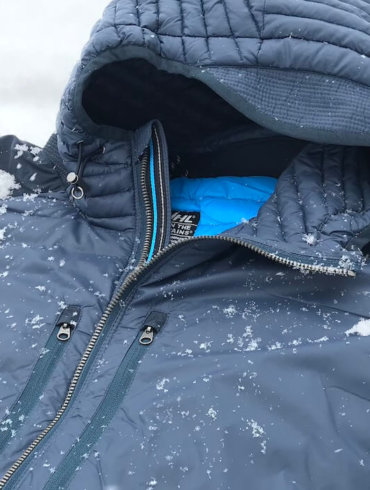 This photo shows a closeup of the KUHL SPYFIRE HOODY down jacket with a small bit of snow.