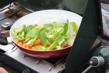 This photo shows a camp stove with a frying pan full of veggies frying outside.