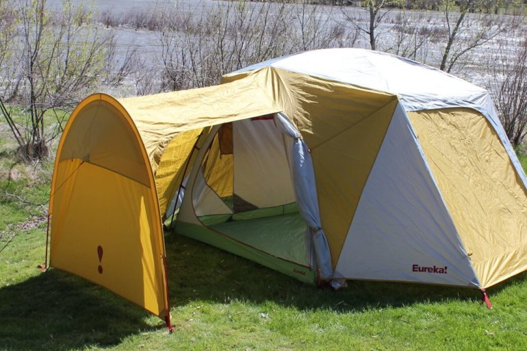 This photo shows the Eureka! Boondocker Hotel 6 Tent set up next to a river at a camping site.