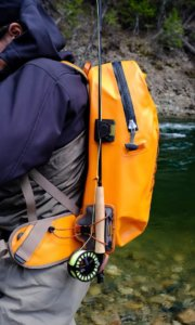 This photo shows a fly fisher wearing a Fishpond Thunderhead Submersible Backpack with the Fishpond Quickshot Rod Holder accessory attached with a fly rod.