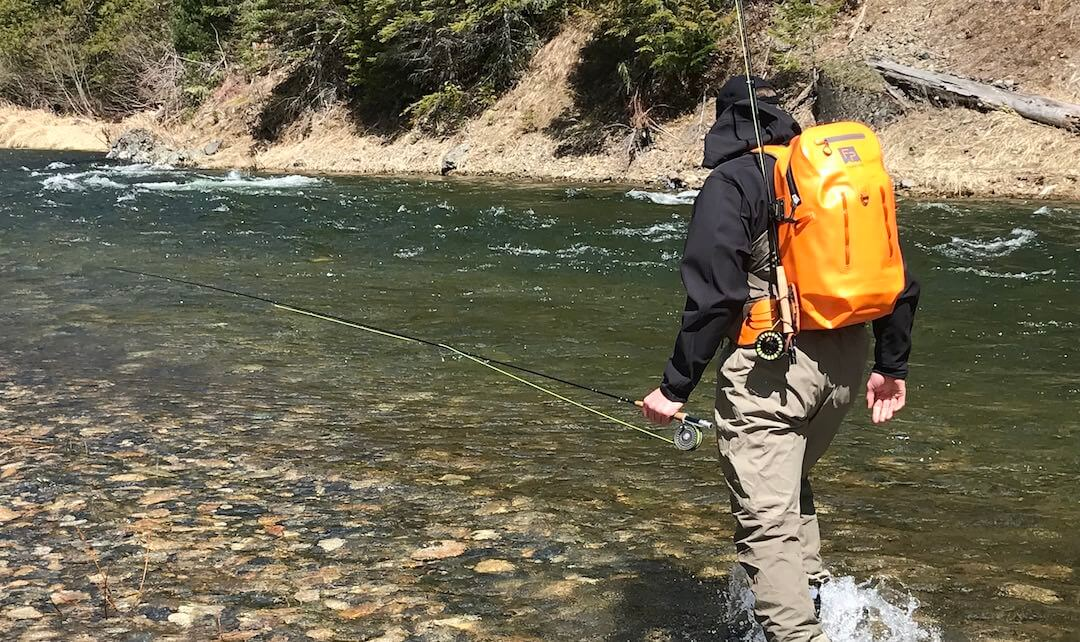 This image shows a fly fisher wearing a Fishpond Thunderhead Submersible Backpack with a Quickshot Rod Holder accessory while wading in a river.