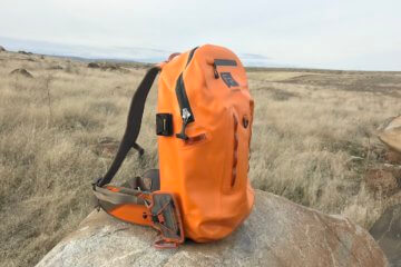 This photo shows the Fishpond Thunderhead Submersible Backpack outside on a rock.