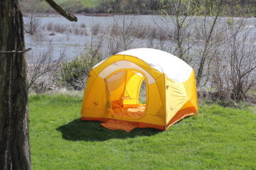 This photo shows the Big Agnes Big House 4 Deluxe camping tent set up near a river.