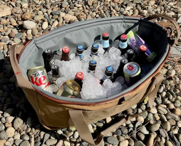 This image shows the Fishpond Ice Storm Soft Cooler full of ice and drinks.