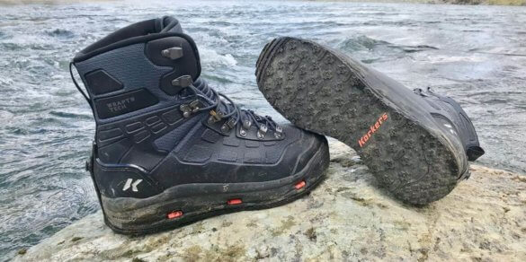 This Korkers WRAPTR review photo shows the Korkers WRAPTR Wading Boots on a boulder by a river.