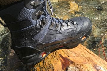 This Korkers WRAPTR review photo shows the Korkers WRAPTR Wading Boots on a wet log.