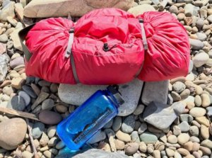 This photo shows the MSR Tour 2 Tent packed into its included stuff sack next to a water bottle as a size comparison.