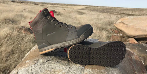 This photo shows the Redington men's Prowler Wading Boots on a rock outside.