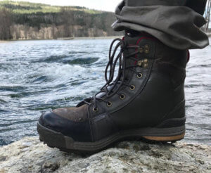This photo shows the Redington men's Wading Boot on a rock next to a river.