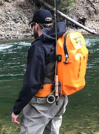 This photo shows an angler wearing a waterproof fishing backpack near a river.